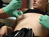 Green gloves pinching nipples
